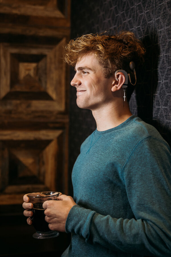 Teenage boy wearing his Deafmetal statement cross hearing aid and cochlear implant jewelry