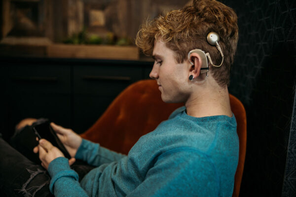 Teenage boy wearing cochlear implant jewelry and earring designed by Deafmetal for the USA collection