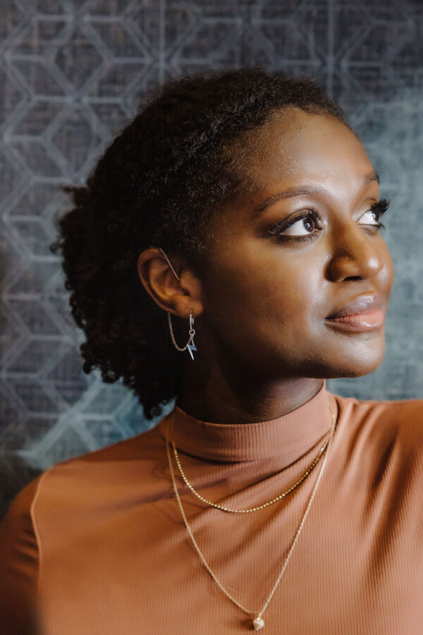 young model wearing hearing aid earrings and jewelry designed for the Deafmetal USA hope collection. This design is the Bolt and can be used as hearing aid and cochlear implant jewelry