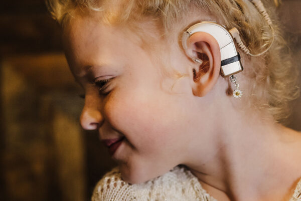 young girl wearing the Daisy flower hearing aid and cochlear implant jewelry designed for the Deafmetal USA Hope collection