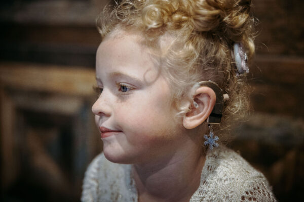 Young child wearing Deafmetal Snowflake cochlear implant and hearing aid jewelry
