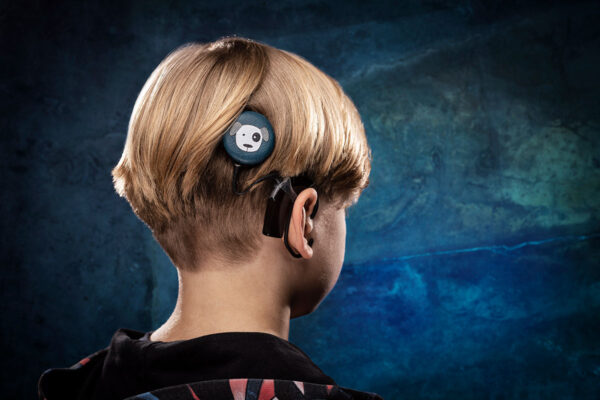 young boy wearing Deafmetal cochlear implant coil hat in leather and in the design of a blue dog