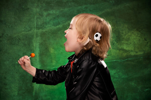 young boy wearing his Deafmetal cochlear implant coil cover in the shape of a soccer ball